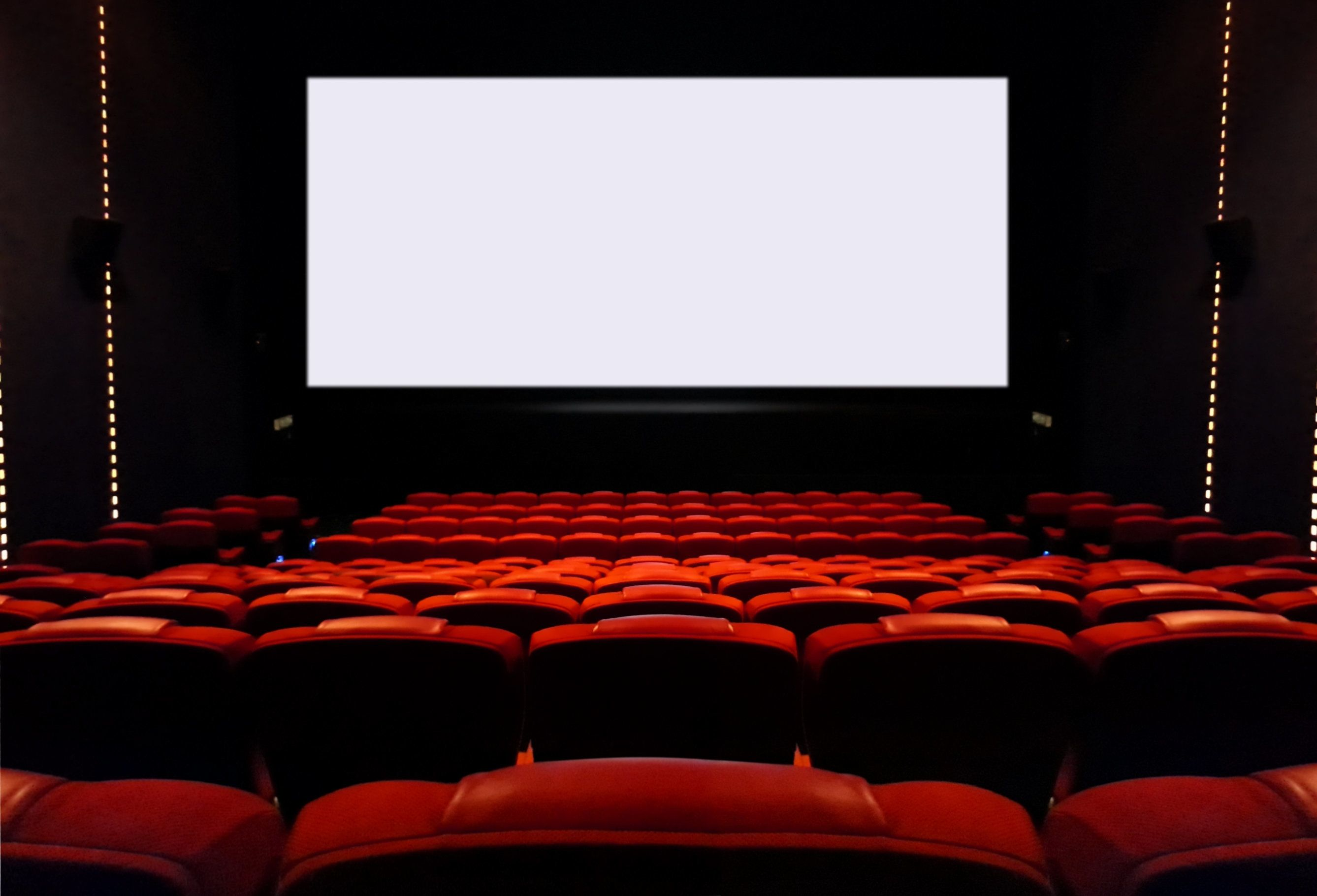 Interior view of empty movie seat and blank cinema screen