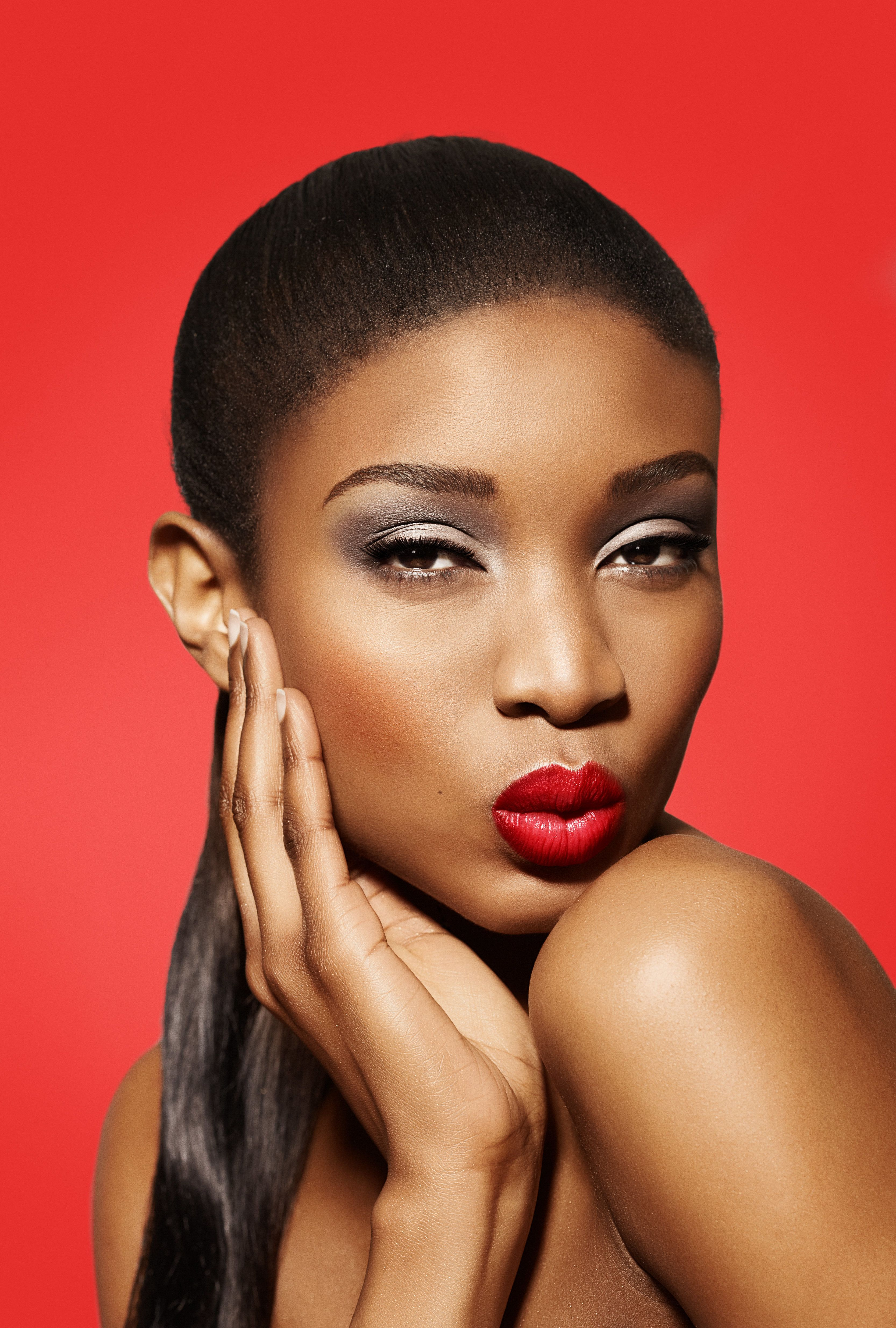 African model with red lipstickon red background.
