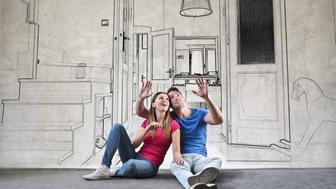 Young couple is sitting on the ground and planning their new home