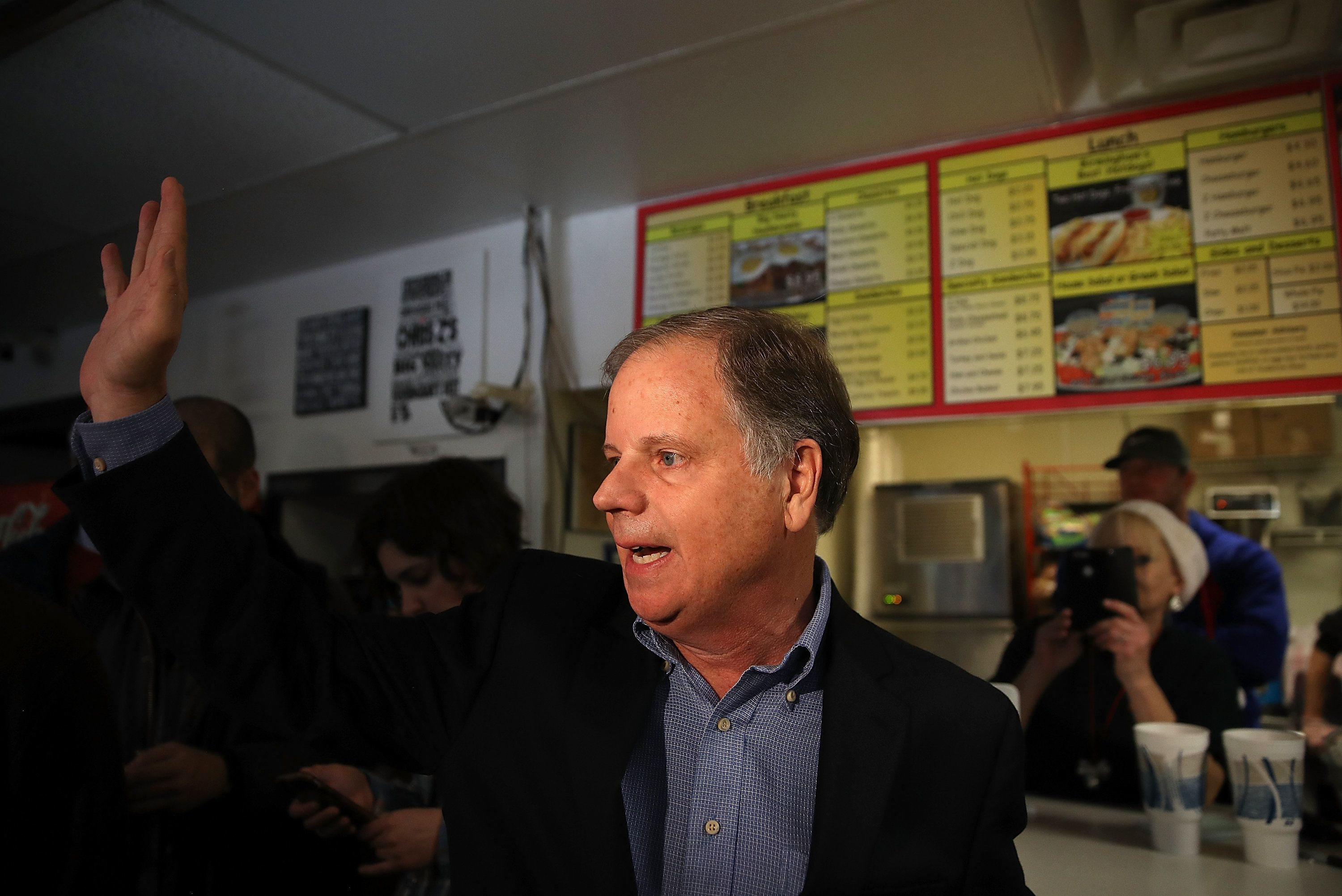 Democratic Senate candidate Doug Jones waves to reporters as he leaves a restaurant in Birmingham, Alabama, Dec. 11, 2017.