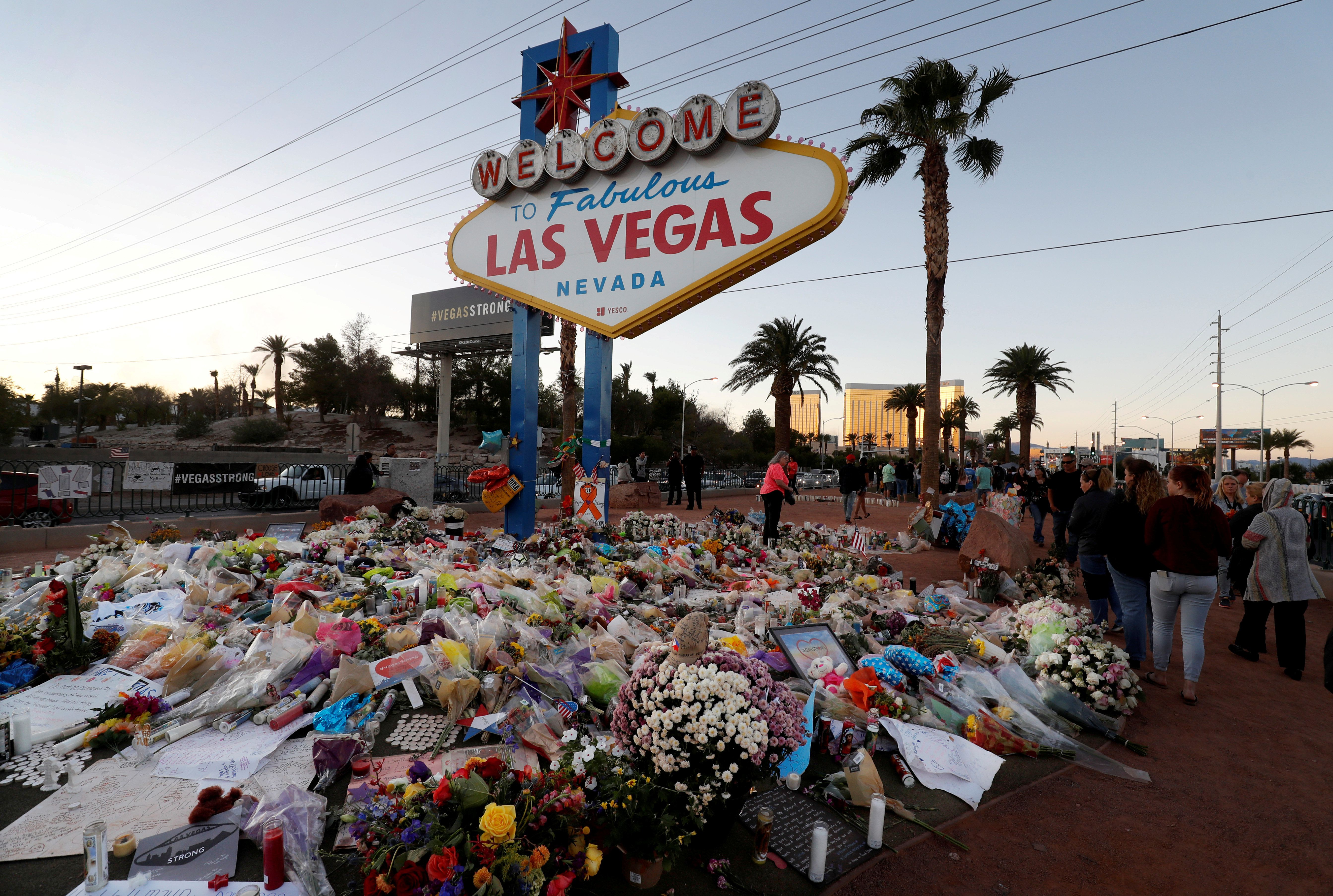 "A makeshift memorial of flowers, candles and messages surrounds the ""Welcome to Las Vegas"" sign in the week after the Oct. 1"