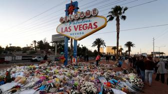 "The ""Welcome to Las Vegas"" sign is surrounded by flowers and items, left after the October 1 mass shooting, in Las Vegas, Nevada U.S. October 9, 2017. REUTERS/Las Vegas Sun/Steve Marcus"