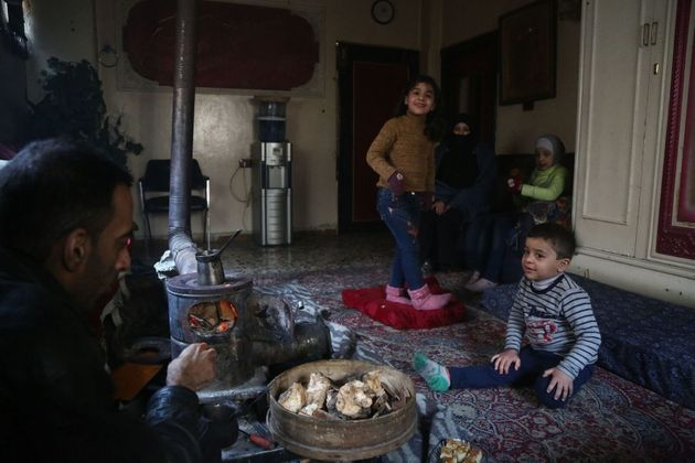 Engie stands in the living room with her family during a cold winter evening in east Ghouta. She suffers...