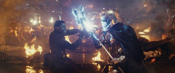 L to R: Finn (John Boyega) battling Captain Phasma (Gwendoline Christie)