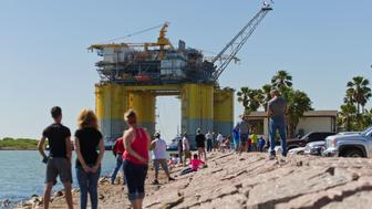 People watch as tug boats transport the Hess Corp. Stampede tension leg oil platform, towed from Kiewit Offshore Services Ltd., in Ingleside, Texas, U.S., on Friday, May 5, 2017. The Stampede deepwater oil and gas field is one of the largest undeveloped fields in the Gulf of Mexico, sitting 115 miles south of Fourchon, Louisiana. Photographer: Eddie Seal/Bloomberg via Getty Images