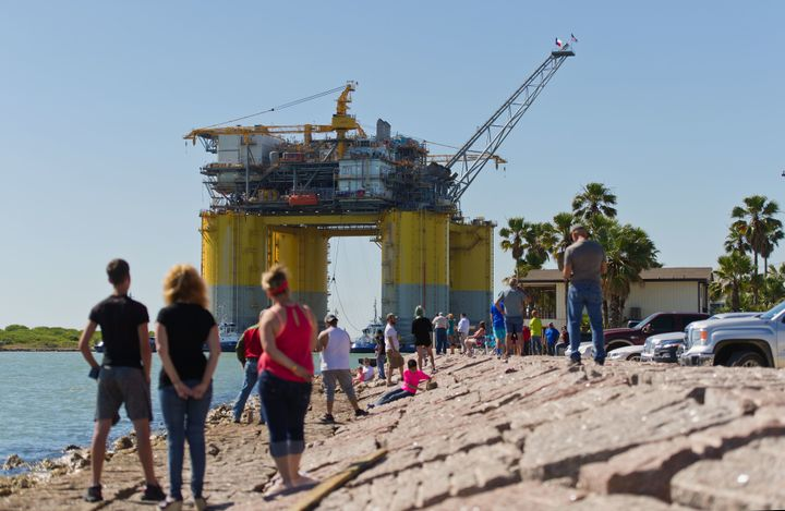 People watch tugboats transport the Hess Corp. Stampede tension leg oil platform on May 5. The Stampede deepwater oil an