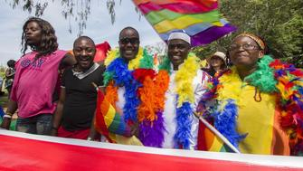 People hold rainbow flags as they take part in the Gay Pride parade in Entebbe on August 8, 2015. Ugandan activists gathered for a gay pride rally, celebrating one year since the overturning of a strict anti-homosexuality law but fearing more tough legislation may be on its way. Homosexuality remains illegal in Uganda, punishable by a jail sentence. AFP PHOTO/ ISAAC KASAMANI        (Photo credit should read ISAAC KASAMANI/AFP/Getty Images)