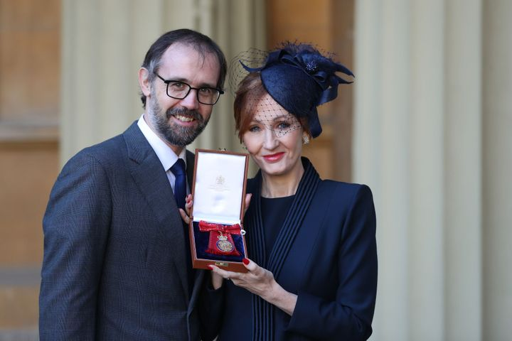 J.K. Rowling, accompanied by her husband Neil Murray, poses with her medal.