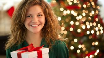 Happy Young Girl Holding Wrapped Present in Living Room.