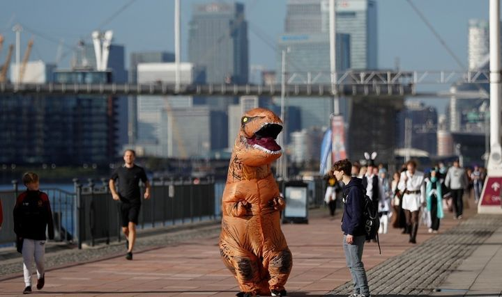 A visitor wearing a T-Rex costume arrives at the London Comic Con.