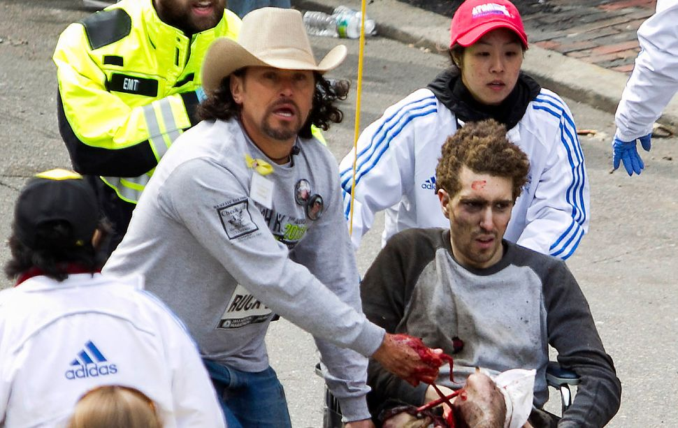 First responders including Carlos Arredondo, in the cowboy hat, tend to Jeff Bauman, who was severely...
