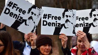 People hold placards with hashtag #FREEDENIZ to protest the detantion of German journalist Deniz Yucel in front of Turkish embassy in Berlin on February 28, 2017.  The investigative detention against Yuecel in Turkey has sparked indignation in the government, parties, and journalist associations in Germany. Yucel, 43, was detained on February 18 and his apartment searched in connection with news reports on an attack by hackers on the email account of Turkey's energy minister. Yucel originates from Floersheim. / AFP / John MACDOUGALL        (Photo credit should read JOHN MACDOUGALL/AFP/Getty Images)