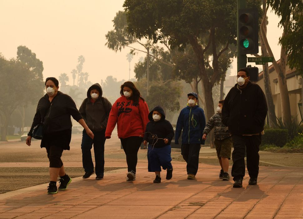 A family wears masks as they walk through the smoke-filled streets after the Thomas fire swept through Ventura County.