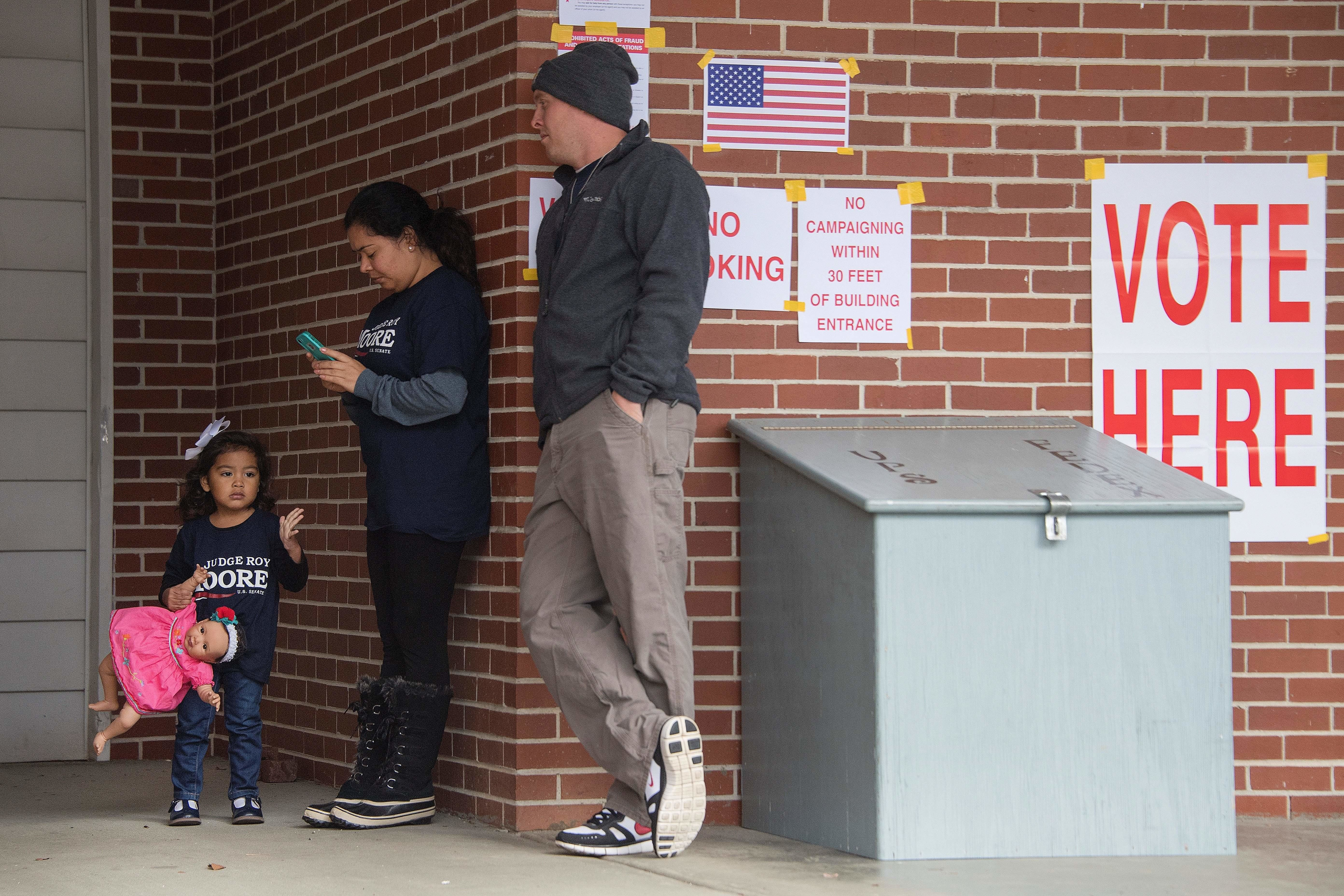 Supporters of Republican Senatorial candidate Roy Moore (L) wait outside a polling station to vote in Gallant, AL, on December 12, 2017. The state of Alabama holds a closely-watched special election for US Senate featuring Republican candidate Roy Moore, who is endorsed by President Donald Trump despite being accused of molesting teenaged girls. / AFP PHOTO / JIM WATSON        (Photo credit should read JIM WATSON/AFP/Getty Images)