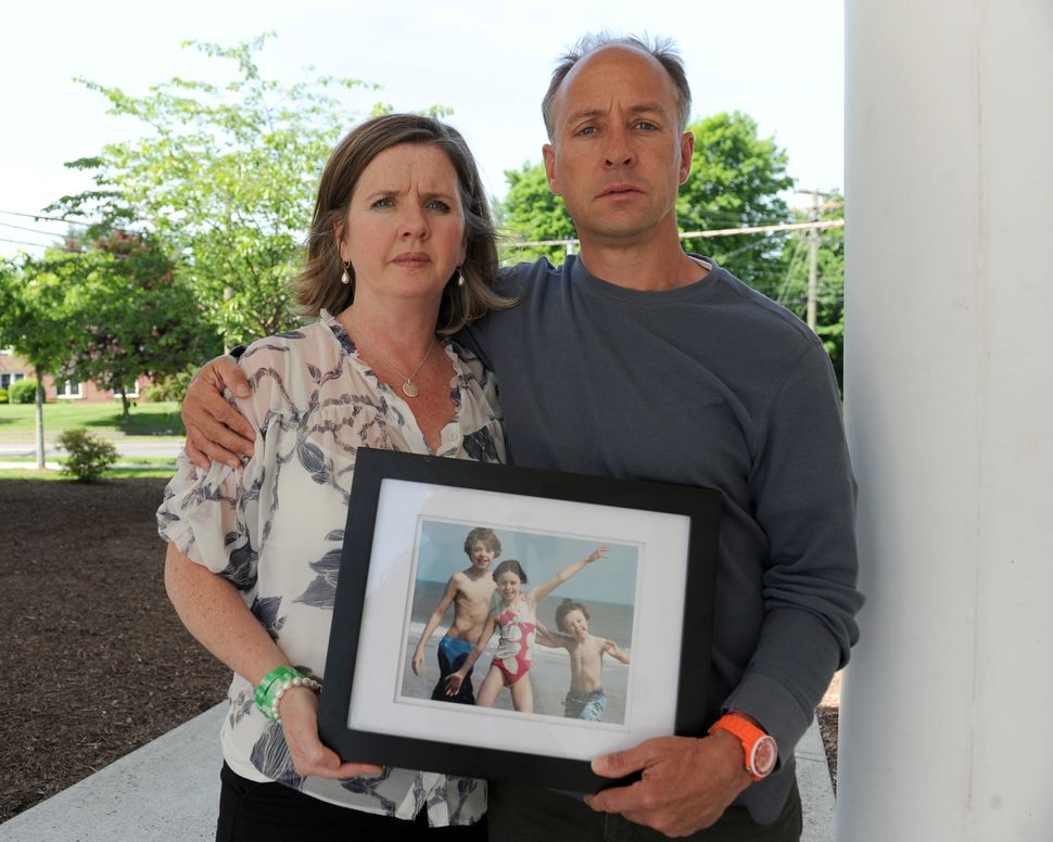Mark Bardenand his wife, Jackie, hold a photo of their children.