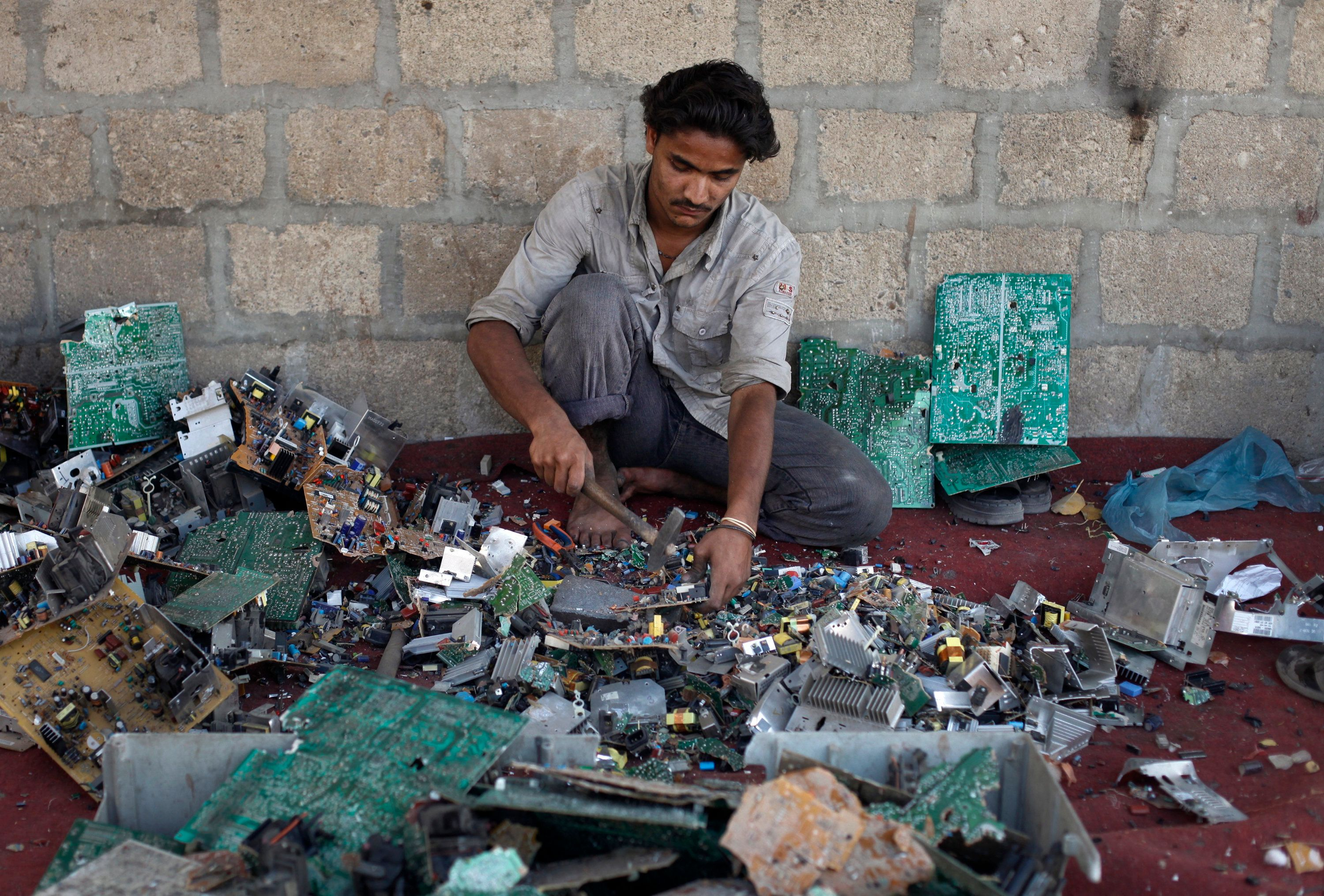 Ali Raza, 21, a scrap worker breaks a computer apart in order to retrieve metal to be used for soldering wires at a makeshift workshop in Karachi April 20, 2011.  REUTERS/Athar Hussain (PAKISTAN - Tags: SOCIETY BUSINESS)
