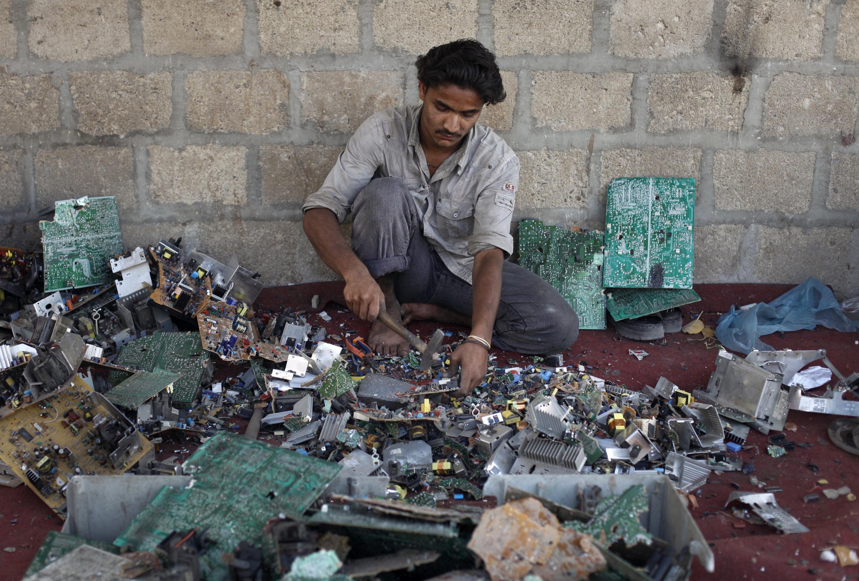 Ali Raza, 21, a scrap worker breaks apart a computer to retrieve metal in a makeshift workshop in Karachi, Pakistan.