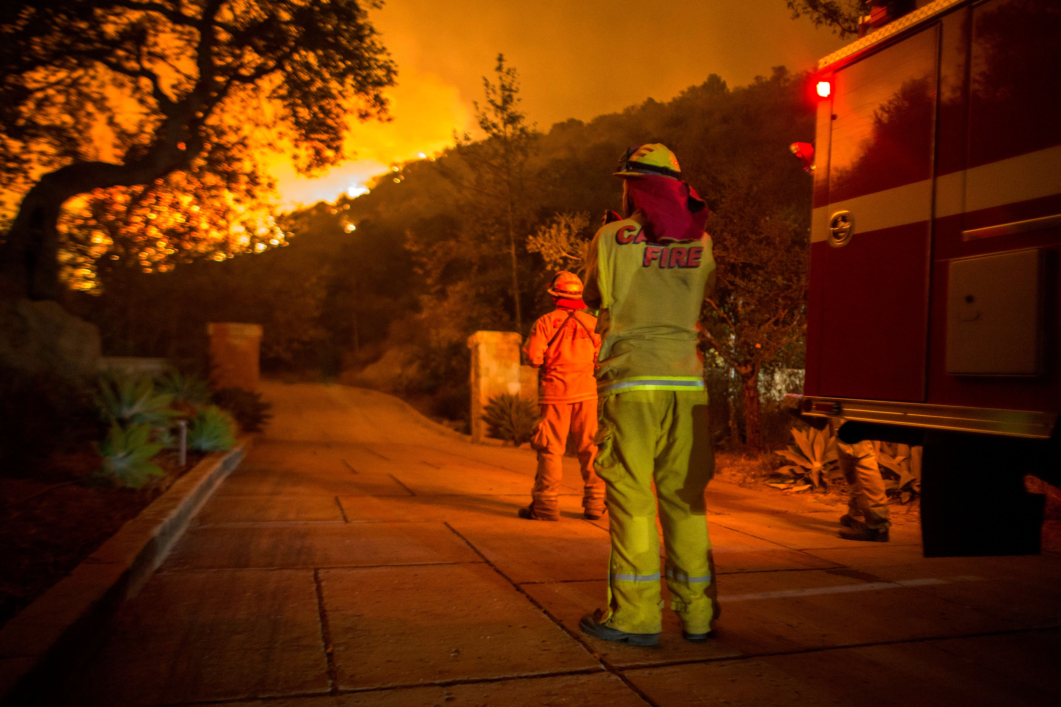 Firefighters watch flames as the Thomas fire approaches homes in Montecito, California on Dec. 12, 2017.