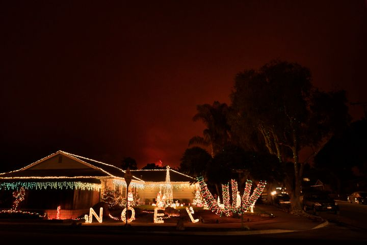 The Thomas wildfire burns behind a home decorated with Christmas lights in Carpinteria, California, on Dec. 11, 2017. Califor