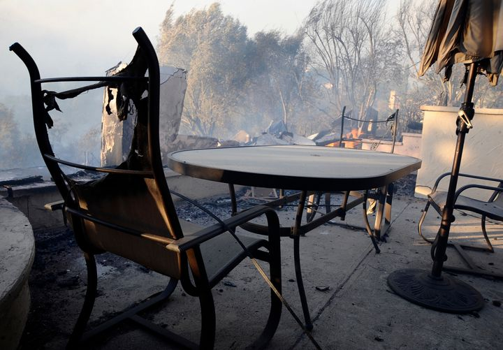 Burnt chairs in front of a swimming pool beside a house destroyed by fire.