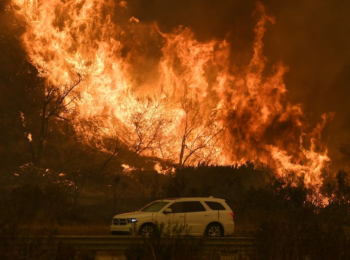 Vehicles pass beside a wall of flames on the 101 highway near Ventura, California, on Dec. 6, 2017.