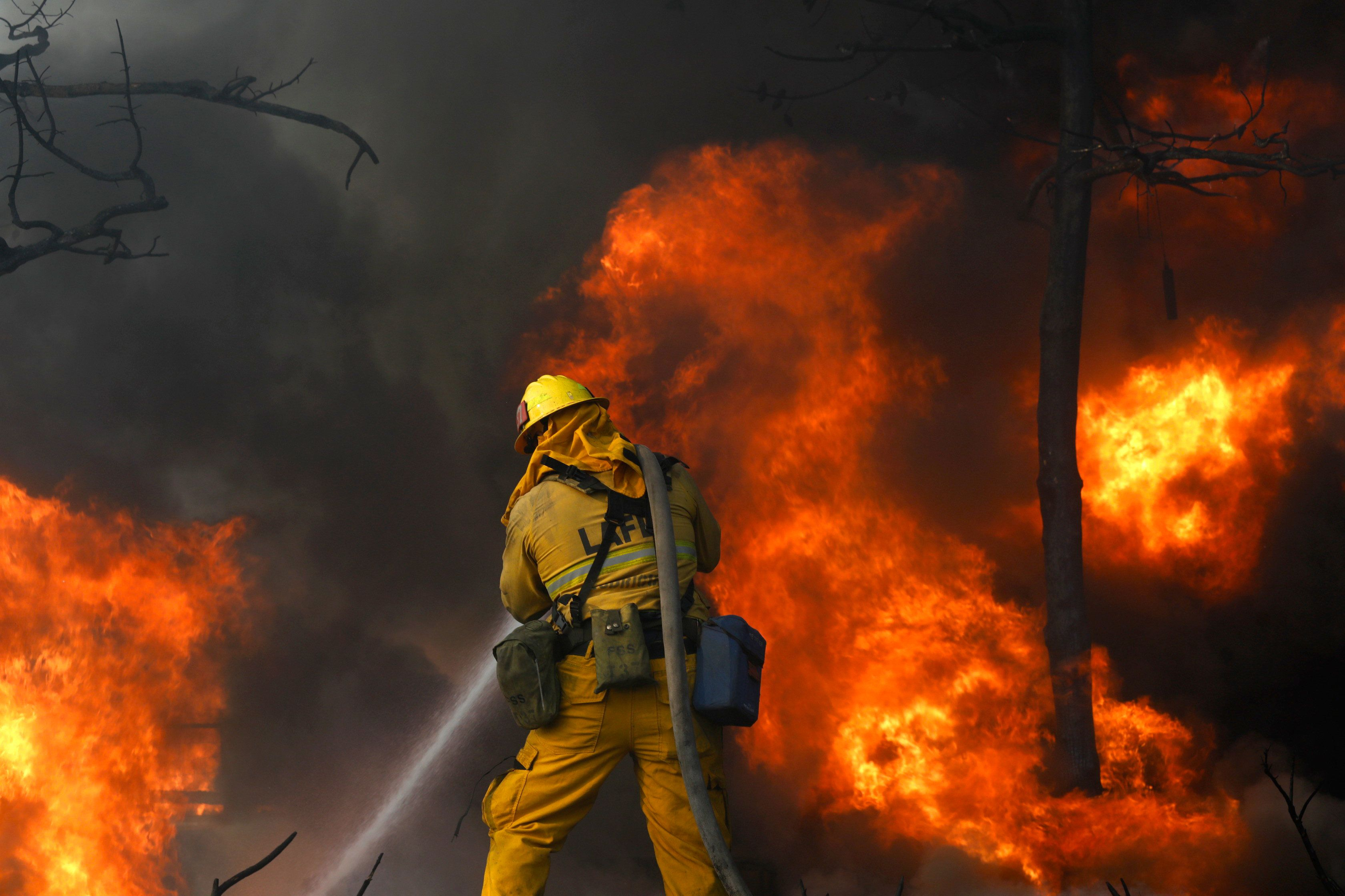 BEL-AIR, CA - DECEMBER 6: Firefighters try and save a home along Linda Flora Dr. in Bel Air, where the Skirball fire prompted a full closure of the 405 Freeway as well as mandatory evacuations in an area of multimillion-dollar homes on December 6, 2017 in Bel-Air, California. (Photo by Genaro Molina / Los Angeles Times via Getty Images)