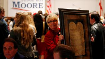 A framed Ten Commandments is being carried by a supporter at Republican Roy Moore's election party in Montgomery, Alabama, U.S., December 12, 2017. REUTERS/Jonathan Bachman