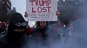 A demonstrator holds a sign in protest of U.S. President Donald Trump near Franklin Square during a demonstration after the 58th presidential inauguration in Washington, D.C., U.S., on Friday, Jan. 20, 2017. Donald Trump became the 45th president of the United States today, in a celebration of American unity for a country that is anything but unified. Photographer: Andrew Harrer/Bloomberg via Getty Images