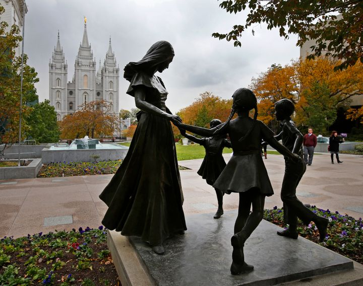A statue of a mother and her children on the main campus of the World Headquarters of the Church of Jesus Christ of Latter-Day Saints, with the Mormon Salt Lake Temple in the background.