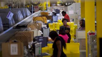 ROBBINSVILLE, NJ - AUGUST 1:  Workers confer at the Amazon Fulfillment Center on August 1, 2017 in Robbinsville, New Jersey.  The more than 1 million square feet facility holds tens of millions of products, features more than 14 miles of conveyor belts, and employs more than 4,000 workers who pick, pack, and ship orders.  Tomorrow Amazon will host a jobs fair to hire 50,000 positions in their fulfillment centers nationwide.  (Photo by Mark Makela/Getty Images)