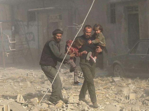 Varios sirios corren entre los escombros de los ataques aéreos en la región de Guta Oriental el 3 de...