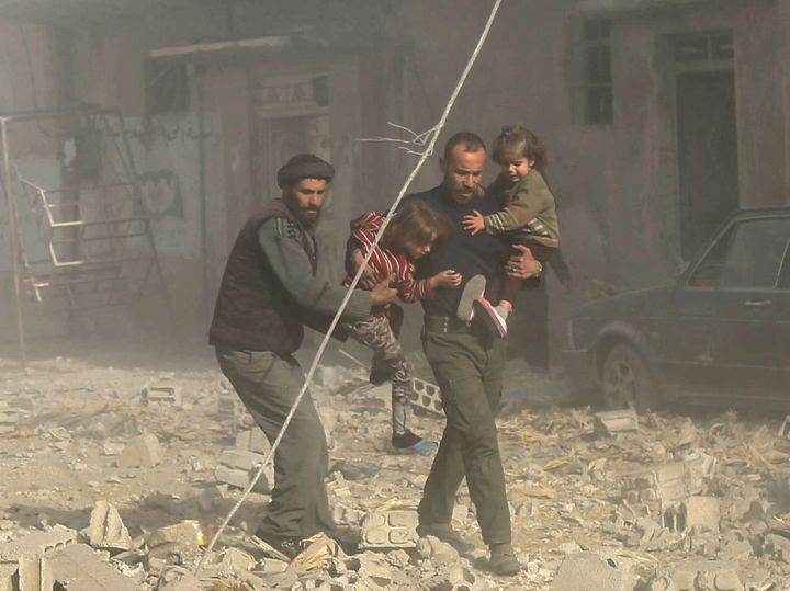 Syrians travel through rubble after airstrikes pounded residential areas in the Eastern Ghouta region on Dec. 3, 2017.