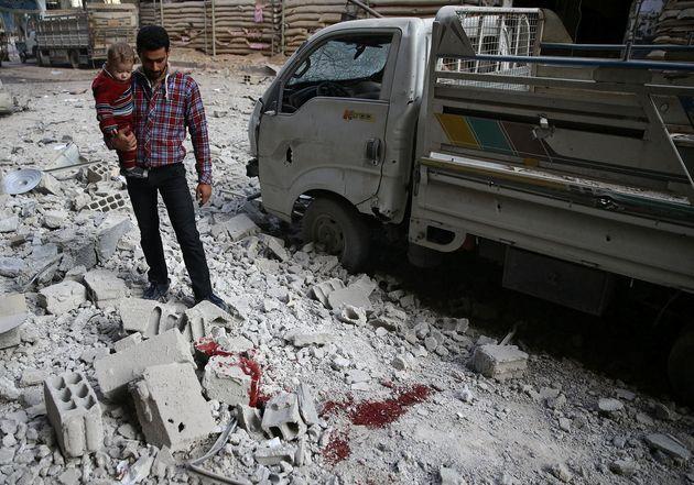 Un hombre y un niño observan los restos de los edificios destrozados por un ataque aéreo en la ciudad...