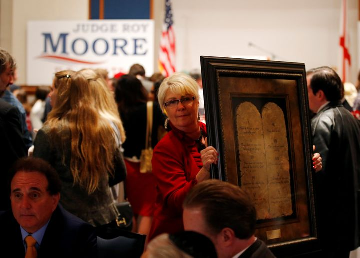 A framed Ten Commandments is being carried by a supporter at Republican Roy Moore's election party in Montgomery, Alaba
