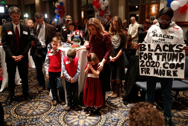 Supporters pray Tuesday during the invocation at Republican U.S. Senate candidate Roy Moore's election...