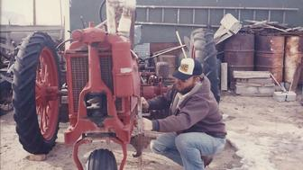 Jim Spencer works on a tractor in the 1980s