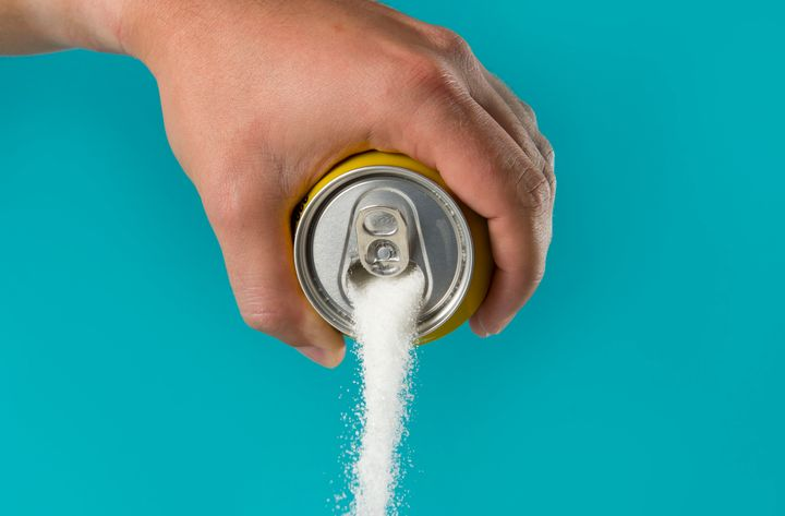 man hand holding lemon refresh drink can pouring sugar stream in sweet and calories content of soda and energy drinks concept in unhealthy nutrition and diet concept