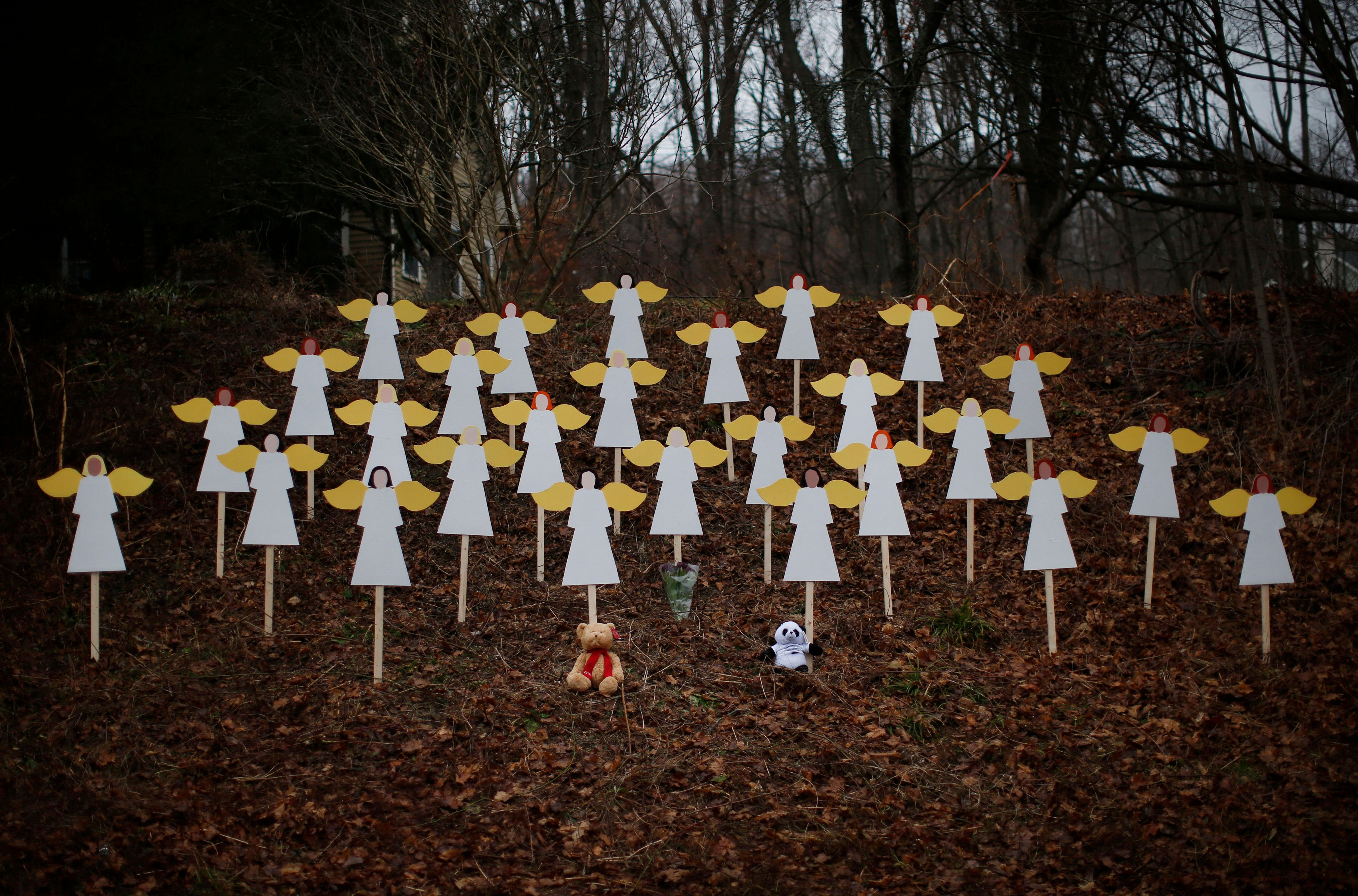 Twenty-seven wooden angel figures are seen placed in a wooded area beside a road near the Sandy Hook Elementary School for the victims of a school shooting in Newtown, Connecticut December 16, 2012. Twelve girls, eight boys and six adult women were killed in the shooting on Friday at the Sandy Hook Elementary School in Newtown.  REUTERS/Mike Segar   (UNITED STATES - Tags: CRIME LAW EDUCATION TPX IMAGES OF THE DAY)