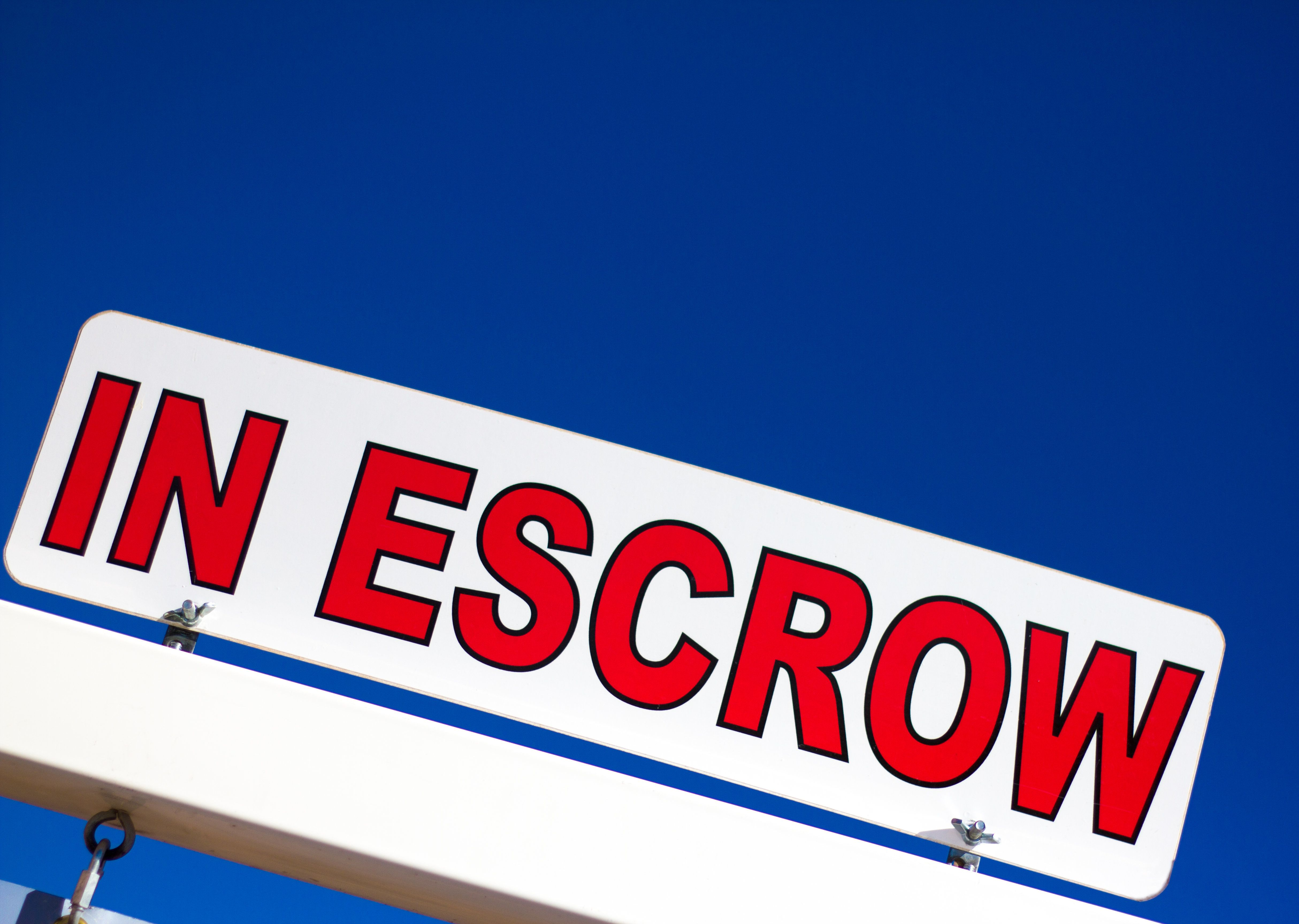 Vibrant red and white 'In Escrow' sign against a brilliant blue sky. Copy space available in the sky.
