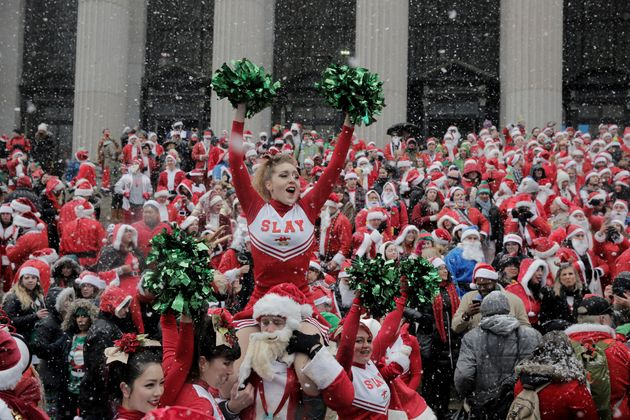 Revellers dressed as Santa Claus and in other holiday themed costumes celebrate during the annual SantaCon...