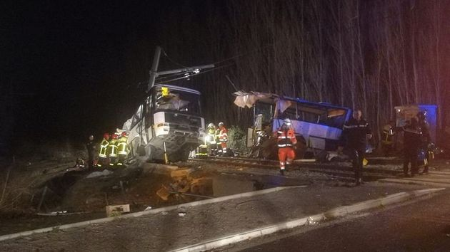 Rescue workers are seen on the site of collision between train and school bus in