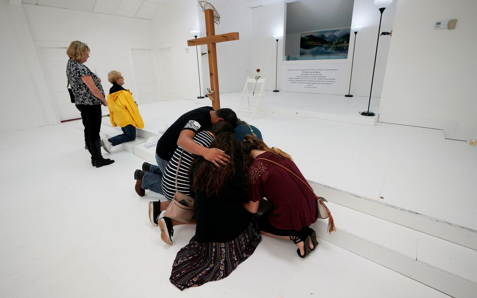 People pray together inside the First Baptist Church of Sutherland Springs, Texas, where ashooter killed 26 people.