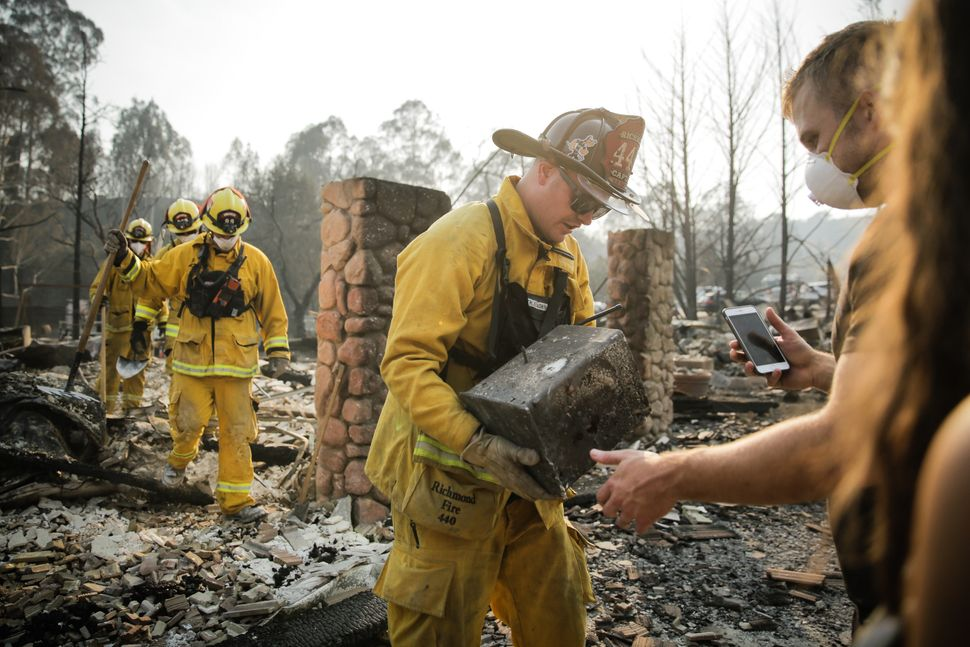 Firefighters help residents of Santa Rosa, California, who lost their homes indevastating wildfires.