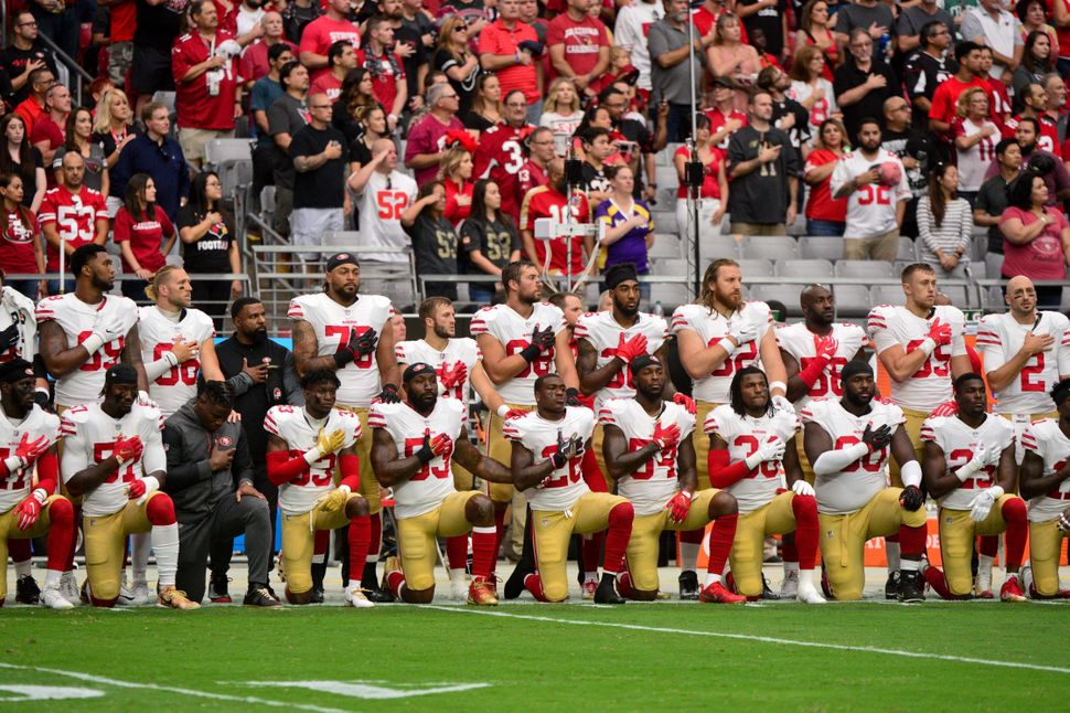 Members of the San Francisco 49ers kneel during the national anthem on Oct. 1, 2017 in Glendale, Arizona.