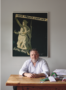 """Chef Stephen Harris backed by his """"I Hate French Cooking"""" poster by Jamie Reid, an artist who worked with the punk band the S"""