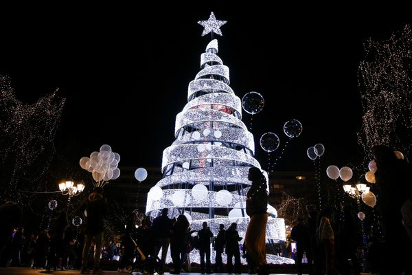 People attend a Christmas tree lighting ceremony at central Syntagma Square in Athens, Greece.