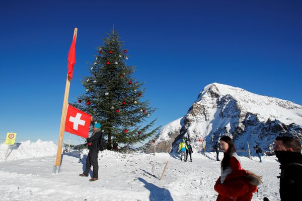 "Tourists pose with a Swiss flag next to a Christmas tree and with the Eiger North Face at the <a href=""https://www.myswissalp"