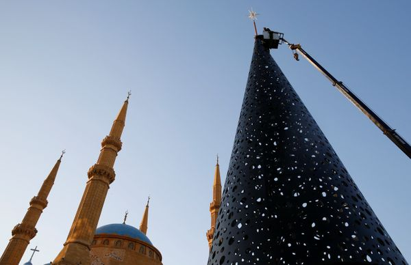 Workers decorate a Christmas tree in front of the Al-Amin mosque in Beirut, Lebanon.