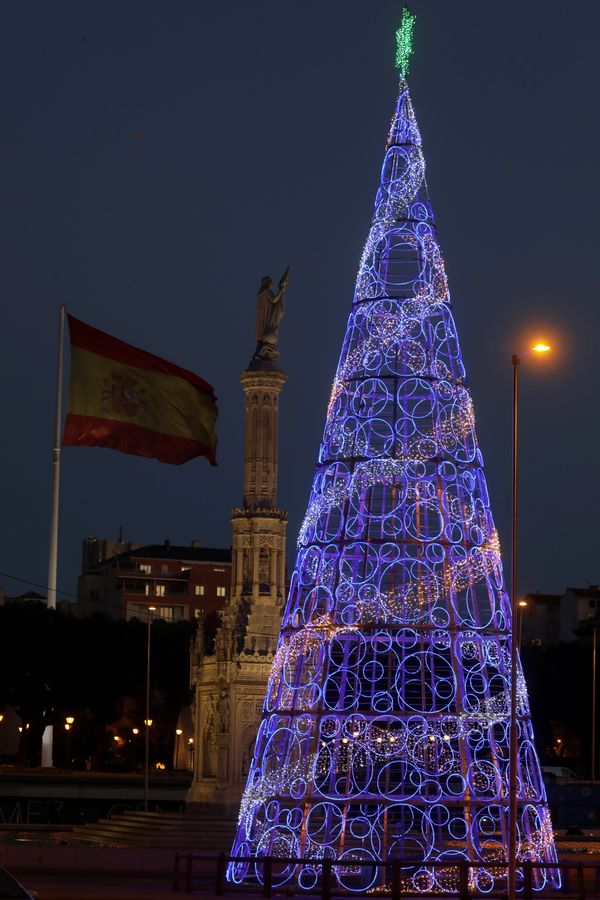 A huge Spanish flag flutters beside a Christopher Columbus statue and a giant Christmas tree in Madrid, Spain.