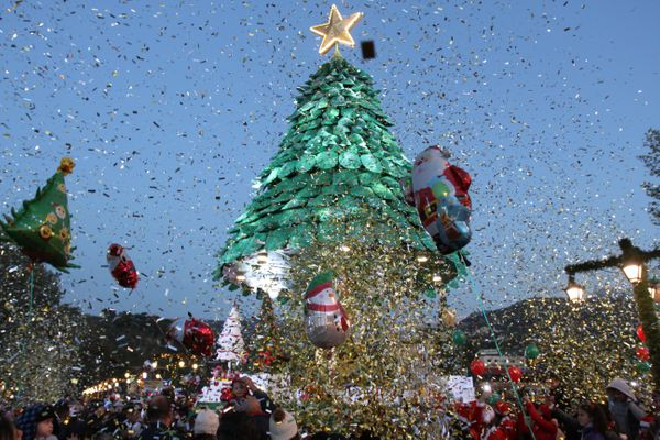 People gather under a Christmas tree, marking the beginning of the Christmas season in Zgharta city, north Lebanon.
